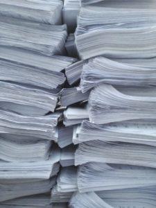 Bundles of documents ready for translation.